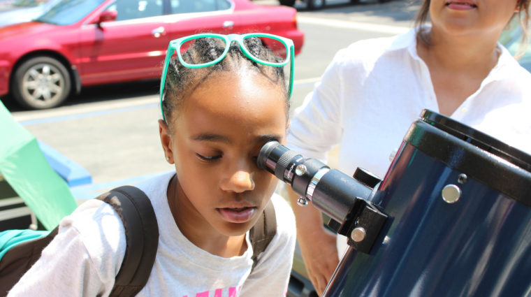 girl with glasses on top of her head looking through a solar telescope