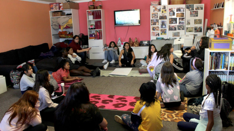 Girls in the YWCA Art and Science Studio sitting in a circle facing one girl